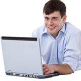 Hombre hermoso, feliz que miente en suelo con el ordenador imagen de archivo
