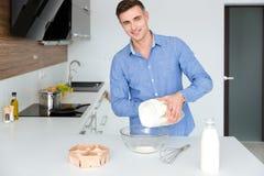 Hombre hermoso feliz que se coloca y que cocina en cocina Imagenes de archivo