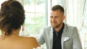 Hombre hermoso feliz que sonríe una fecha, par feliz en la cafetería que mira uno a almacen de metraje de vídeo