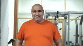 Hombre hermoso gordo en un gimnasio en la camiseta anaranjada que se coloca y que parece coqueta a la cámara