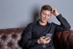Hombre hermoso joven atractivo que lleva la sentada negra de la camisa en el smartphone de cuero de la tenencia del sof? Comodida fotos de archivo libres de regalías
