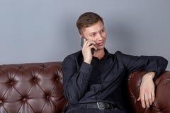 Hombre hermoso joven atractivo que lleva la sentada negra de la camisa en el smartphone de cuero de la tenencia del sof? Comodida imagenes de archivo