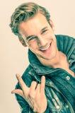 Hombre hermoso joven con gesto del rock-and-roll Foto de archivo libre de regalías