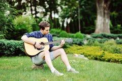Hombre hermoso joven con la guitarra al aire libre Imagenes de archivo