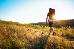 Hombre hermoso joven con la mochila que viaja en barranco en la puesta del sol Imagenes de archivo