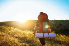 Hombre hermoso joven con la mochila que viaja en barranco en la puesta del sol Foto de archivo libre de regalías