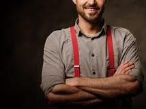 Hombre hermoso joven con las ligas que llevan de la barba y presentación en fondo oscuro Foto de archivo libre de regalías