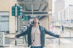 Hombre hermoso joven con los auriculares que presentan en las calles de la ciudad Fotografía de archivo