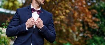 Hombre hermoso joven con una barba en camisa blanca lujosa y chaqueta azul con el bowtie Foto de archivo libre de regalías