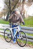 Hombre hermoso joven con una bicicleta Fotos de archivo