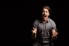 Hombre hermoso joven de Dissapointed que gesticula, gritando sobre fondo negro Fotos de archivo