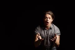 Hombre hermoso joven de Dissapointed que gesticula, gritando sobre fondo negro Fotos de archivo libres de regalías