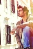 Hombre hermoso joven de la ciudad Modelo que se sienta urbano Edificio Windows Imagen de archivo libre de regalías
