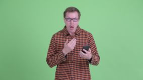 Hombre hermoso joven del inconformista usando el teléfono y el parecer sorprendido almacen de video