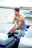 Hombre hermoso joven del marinero que conduce su barco de motor Foto de archivo