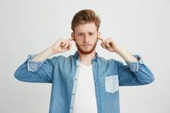 Hombre hermoso joven descontentado con los oídos cerrados que fruncen el ceño de la barba sobre el fondo blanco Foto de archivo libre de regalías