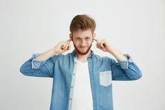 Hombre hermoso joven descontentado con los oídos cerrados que fruncen el ceño de la barba sobre el fondo blanco Imagen de archivo