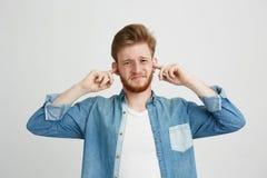 Hombre hermoso joven descontentado con los oídos cerrados que fruncen el ceño de la barba sobre el fondo blanco Fotos de archivo