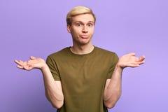 Hombre hermoso joven desorientado y desconcertado que confunde la expresi?n foto de archivo libre de regalías