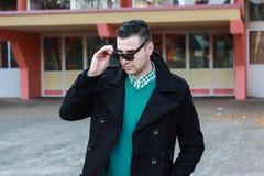 Hombre hermoso joven en el abrigo de invierno negro que quita las gafas de sol Foto de archivo libre de regalías