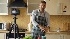 Hombre hermoso joven en el blog video de la comida del tiroteo del delantal sobre cocinar en cámara del dslr en cocina imagenes de archivo
