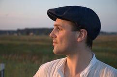 Hombre hermoso joven en el casquillo, portait Salida del sol Imagen de archivo libre de regalías
