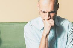 Hombre hermoso joven en la camisa con la expresión triste de la cara que siente presionada y desgraciada mientras que él que pien imagenes de archivo