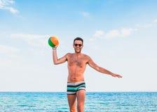 Hombre hermoso joven en la playa trowing la bola Fotografía de archivo libre de regalías