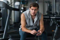 Hombre hermoso joven en ropa de deportes usando su teléfono elegante mientras que teniendo resto en gimnasio Fotos de archivo