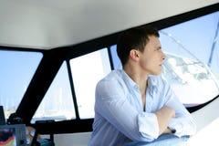 Hombre hermoso joven en un interior del barco del yate Imagen de archivo