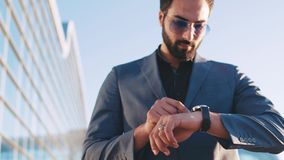 Hombre hermoso joven en un traje que pasa por el terminal de aeropuerto y que usa el reloj elegante Dispositivos modernos, forma  metrajes