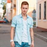 Hombre hermoso joven en una camisa del dril de algodón y vaqueros en el fondo Foto de archivo