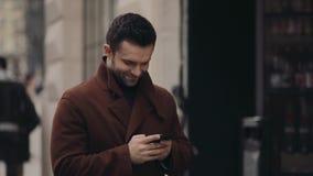 Hombre hermoso joven en una capa de moda que se coloca en el centro de ciudad y que usa su teléfono para la navegación por Intern almacen de video