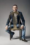 Hombre hermoso joven en una silla Imagen de archivo libre de regalías