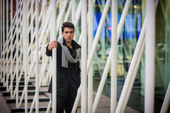 Hombre hermoso joven entre las barras de metal blanco Foto de archivo libre de regalías