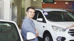 Hombre hermoso joven feliz que presenta con su nuevo coche que muestra llaves almacen de video