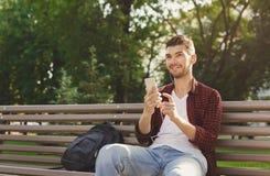 Hombre hermoso joven feliz que se sienta al aire libre y que usa smartphone Fotografía de archivo libre de regalías