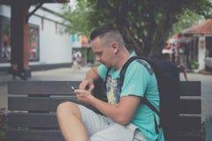 Hombre hermoso joven feliz que se sienta en el banco al aire libre y que usa smartphone Isla tropical de Bali, Indonesia Fotografía de archivo libre de regalías
