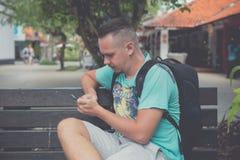 Hombre hermoso joven feliz que se sienta en el banco al aire libre y que usa smartphone Isla tropical de Bali, Indonesia Imagenes de archivo