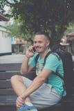 Hombre hermoso joven feliz que se sienta en el banco al aire libre y que usa smartphone Isla tropical de Bali, Indonesia Imágenes de archivo libres de regalías