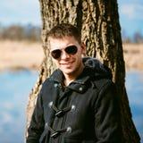 Hombre hermoso joven inclinado contra árbol por el río en Autumn Day C Imagenes de archivo