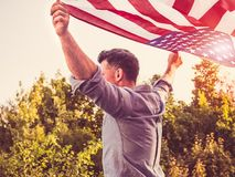 Hombre hermoso, joven que agita una bandera americana foto de archivo libre de regalías