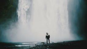 Hombre hermoso joven que camina cerca de la cascada potente de Gljufrabui en Islandia solamente, disfrutando de paisaje almacen de video