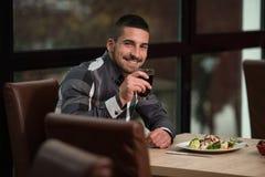 Hombre hermoso joven que cena en un restaurante Foto de archivo