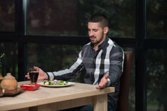 Hombre hermoso joven que cena en un restaurante Imagen de archivo