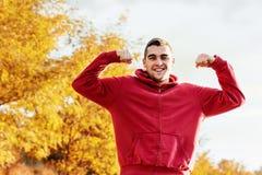 Hombre hermoso joven que dobla los mucles al aire libre Imagenes de archivo