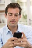 Hombre hermoso joven que escribe SMS en el teléfono móvil. imágenes de archivo libres de regalías