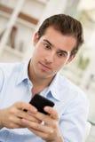 Hombre hermoso joven que escribe SMS en el teléfono móvil. fotos de archivo libres de regalías