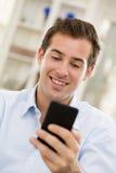 Hombre hermoso joven que escribe SMS en el teléfono móvil. imagen de archivo