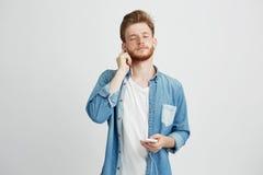 Hombre hermoso joven que escucha fluir música en auriculares con los ojos cerrados que gozan sobre el fondo blanco Foto de archivo